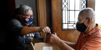 Suzie Roach, wife of First Primitive Methodist Church of Nanticoke Pastor Joe Roach, hands bags of take-out Thanksgiving meals to Gerald Mech on Thursday.                                  Fred Adams | For Times Leader