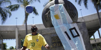 Marcio Pereira, 57, who likes to go by the nickname 'Pele' juggles a soccer ball next to a monument adorned with a national Argentine flag bearing the No. 10, placed there by a mourner as a tribute to Diego Maradona, outside the Maracana stadium in Rio de Janeiro, Brazil, on Thursday. Maradona died on Wednesday at the age of 60 of a heart attack in a house outside Buenos Aires where he recovered from a brain operation.                                  AP photo