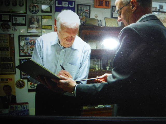 <p>Laurence Cook treasures a copy of this photograph that shows President Jimmy Carter signing his autograph.</p>