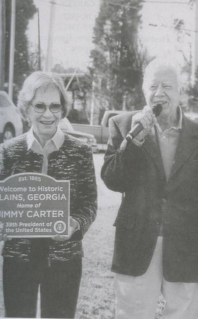 <p>This photo, included in 'Symbols of Patriotism,' shows President and Mrs. Carter at a 2014 ceremony during which a new town sign for Plains, Ga., was dedicated. Local author Laurence L. Cook and his wife, Diane, managed the sign project.</p>
