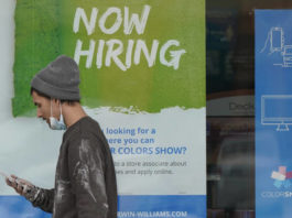 A man walks past a 'Now Hiring' sign on a window at Sherwin Williams store Friday in Woodmere Village, Ohio. Massive fraud in the nation's unemployment system is raising alarms even as President Joe Biden and Congress prepare to pour hundreds of billions more into expanded benefits for those left jobless by the coronavirus pandemic.