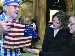 In this Nov. 11, 2012, still image from the film 'Etched in Glass: The Legacy of Steve Ross,' provided by Many Hats Productions, Holocaust survivor Steve Ross, from left, displays an American flag to Brenda Sattler and Gwen Sattler Allanson at a Veterans Day event at the Statehouse in Boston. Ross was given the flag by U.S. Army Lt. Steve Sattler during the April 1945 liberation of the Nazi concentration camp Dachau in Germany. Brenda Sattler is the granddaughter of Lt. Sattler, while Gwen Sattler Allanson is the daughter of Lt. Sattler.                                  Tony Bennis | Many Hats Productions via AP