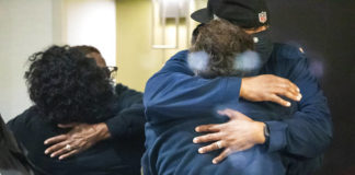 People hug after learning that their loved one is safe after a shooting inside a FedEx building Friday, April 16, 2021. Multiple people were shot and killed in a late-night shooting at a FedEx facility in Indianapolis, and the shooter killed himself, police said.(The Indianapolis Star via AP)