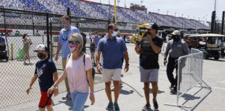 Fans walk through the garage area before a NASCAR Cup Series race at Darlington Raceway on Sunday in Darlington, S.C. It is the first time this year that fans are allowed back in the garage area.                                  AP photo