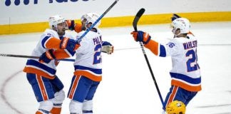The New York Islanders' Kyle Palmieri, center, celebrates with Nick Leddy (2) and Oliver Wahlstrom (26) after putting a shot over Pittsburgh Penguins goaltender Tristan Jarry for the game-winning goal in overtime in Game 1 of an NHL Stanley Cup first-round playoff series in Pittsburgh on Sunday. The Islanders won 4-3.                                  AP photo