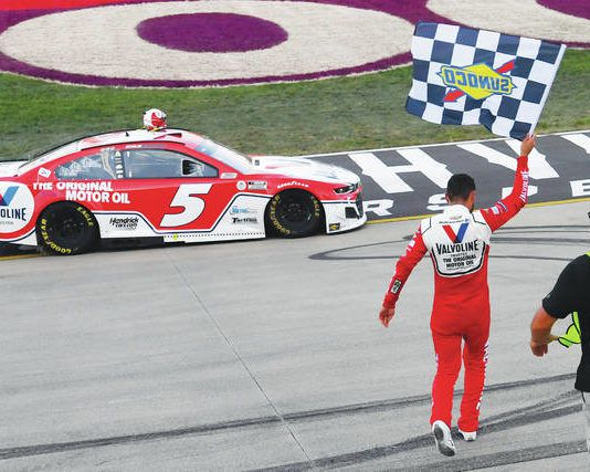 Kyle Larson walks back to his car with the checkered flag after winning Sunday at Nashville, his third straight Cup Series victory.                                  John Amis   AP photo