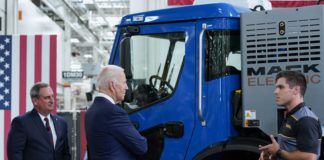 Mack Trucks President Martin Weissburg, left, and President Joe Biden listen as Jake Evans, end-to-end Specialist for Conventional Assembly Operations, right, speaks as Biden tours the Lehigh Valley operations facility for Mack Trucks in Macungie on Wednesday.                                  Susan Walsh   AP photo