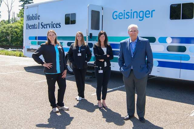 Geisinger Health Plan's dental health team stands in front of the mobile unit. From left, Rachel Chesney and Cortney Young, public health dental hygiene practitioners; and dentists Kristen Schintz and Michael Halupa, medical directors of dental medicine.                                  Submitted