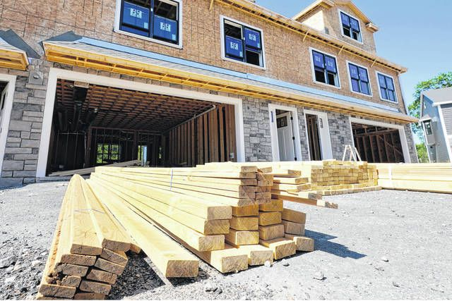 Lumber is piled at a housing construction site in Middleton, Mass. Wood prices have skyrocketed over the last year, leaving would-be home renovators deciding whether to wait out the high costs or move forward on a project that's more expensive than it would have been a year ago.                                  AP photo