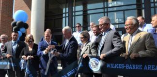 District superintendent Brian Costello and School Board President Joe Caffrey officially cut the ribbon for the new Wilkes-Barre Area High School in Plains Township on Thursday.                                  Mark Guydish | Times Leader