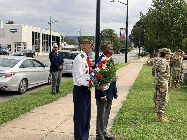 Kevin Armitage (left) and Commander Lucius Washington, both of AMVETS Post 59 in Hanover Township, wait to present a ceremonial wreath in honor of the 33 109th Field Artillery soldiers killed in a train crash on Sept. 11, 1950.                                  Kevin Carroll   Times Leader