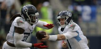 Tennessee Titans quarterback Ryan Tannehill, right, hands off to running back Derrick Henry during the second half of an NFL game against the Seattle Seahawks on Sunday in Seattle. The Titans won 33-30 in overtime.                                  AP photo