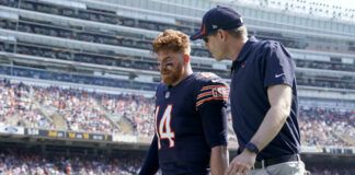 Chicago Bears quarterback Andy Dalton walks to the locker room with an unidentified trainer during the first half of an NFL game against the Cincinnati Bengals on Sunday in Chicago.                                  AP photo