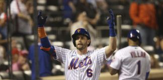 The New York Mets' Jeff McNeil celebrates as he returns to the dugout after hitting a home run during the seventh inning of a game against the Philadelphia Phillies on Sunday in New York.                                  AP photo