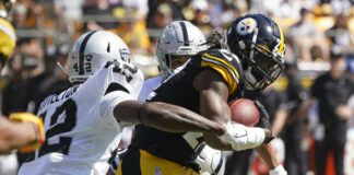 Pittsburgh Steelers running back Najee Harris is tackled by Las Vegas Raiders inside linebacker Cory Littleton (42) and defensive back Johnathan Abram, rear, during the first half of an NFL game in Pittsburgh on Sunday.                                  AP photo