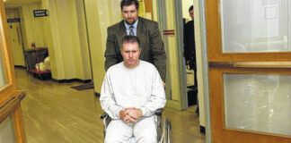03/06/06— Scott Bolton is wheeled out from the Luzerne County Courthouse by county detective Chris Lynch to awaiting transport to the county prison at the conclusion of a court proceeding. Times Leader file
