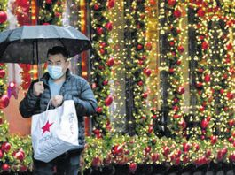 FILE -In this Nov. 30, 2020 file photo, a shopper walks by a holiday window display in New York.                                  AP file photo